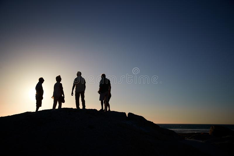 Silhouette Of Senior Friends Standing On Rocks By Sea On Vacation At Sunset stock images