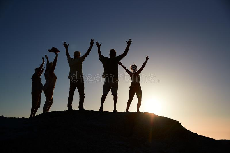 Silhouette Of Senior Friends Standing On Rocks By Sea On Vacation At Sunset With Arms Outstretched royalty free stock photos