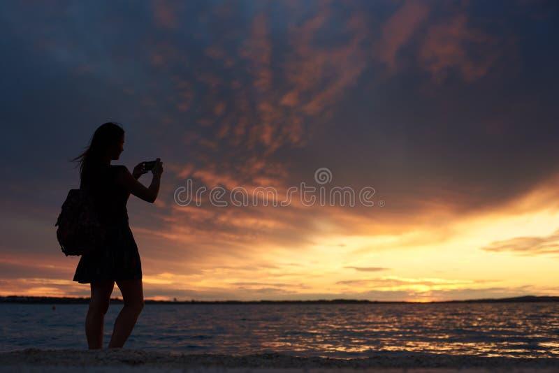 Silhouette seule de femme au bord de l'eau, appréciant le beau paysage marin au coucher du soleil images stock