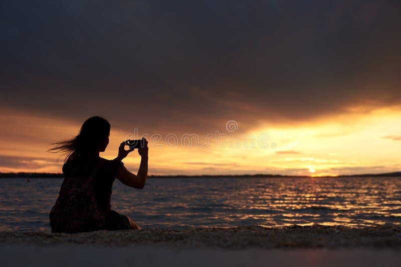 Silhouette seule de femme au bord de l'eau, appréciant le beau paysage marin au coucher du soleil photos stock