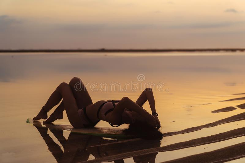 Silhouette girl in swimsuit lying and posing on surf board at beach during sunset royalty free stock image