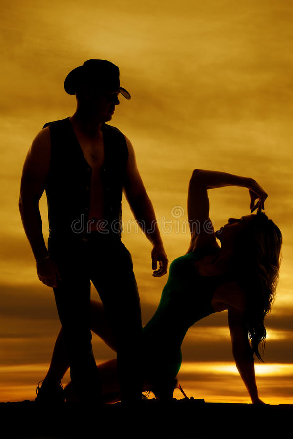 Silhouette of a woman sitting on heel looking up at cowboy stock image