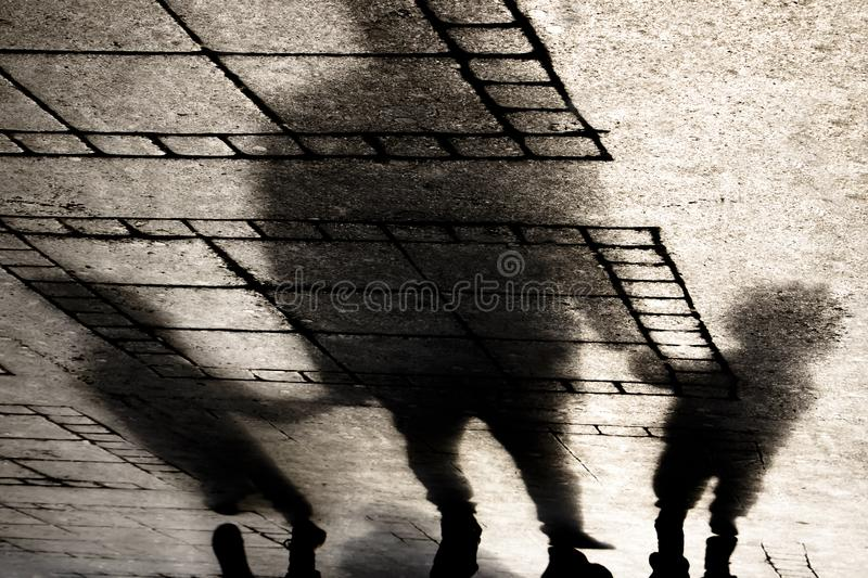 Silhouette shadow of a father holding hands with two small boys. Sons on city sidewalk in sepia black and white royalty free stock image