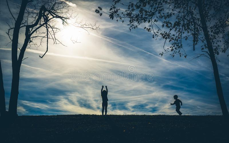 Silhouette shadows of two children on a hill with a blue sky behind them. While playing royalty free stock images