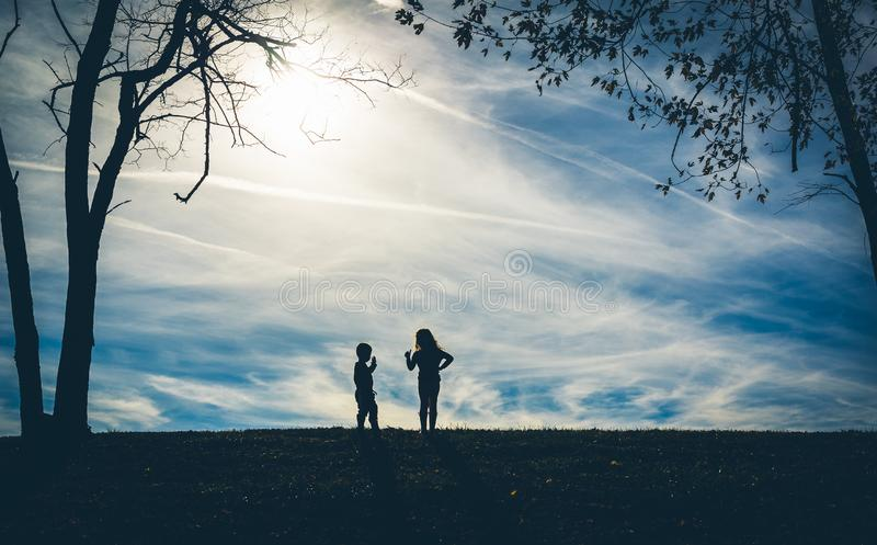 Silhouette shadows of two children on a hill with a blue sky behind them. While playing stock photography