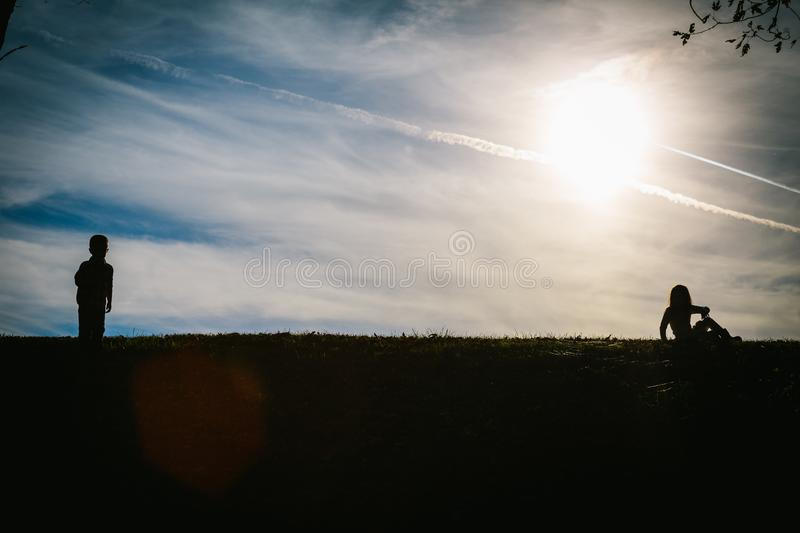 Silhouette shadows of two children on a hill with a blue sky behind them. While playing royalty free stock photography