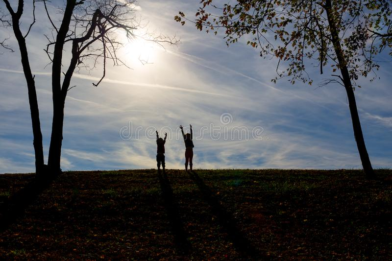 Silhouette shadows of two children on a hill with a blue sky behind them. While playing royalty free stock photos