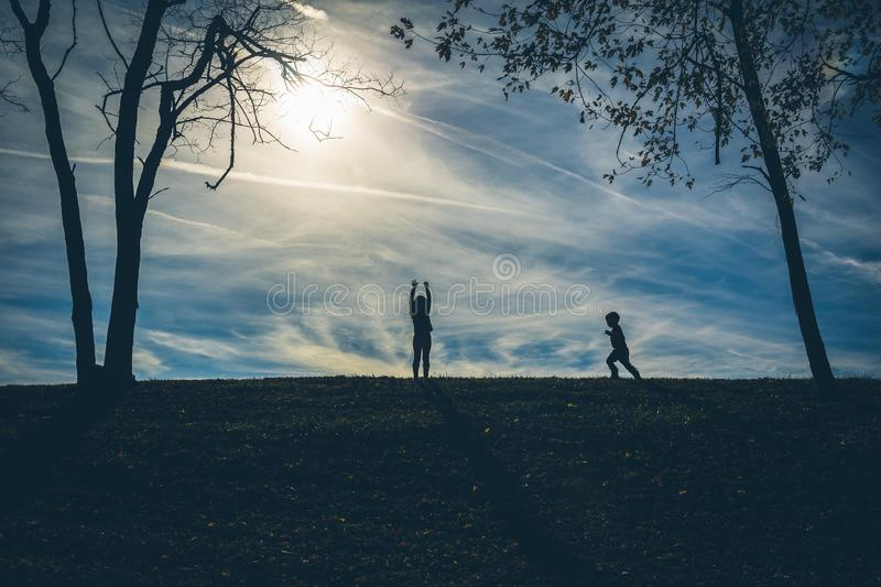Silhouette shadows of two children on a hill with a blue sky behind them. While playing royalty free stock photo