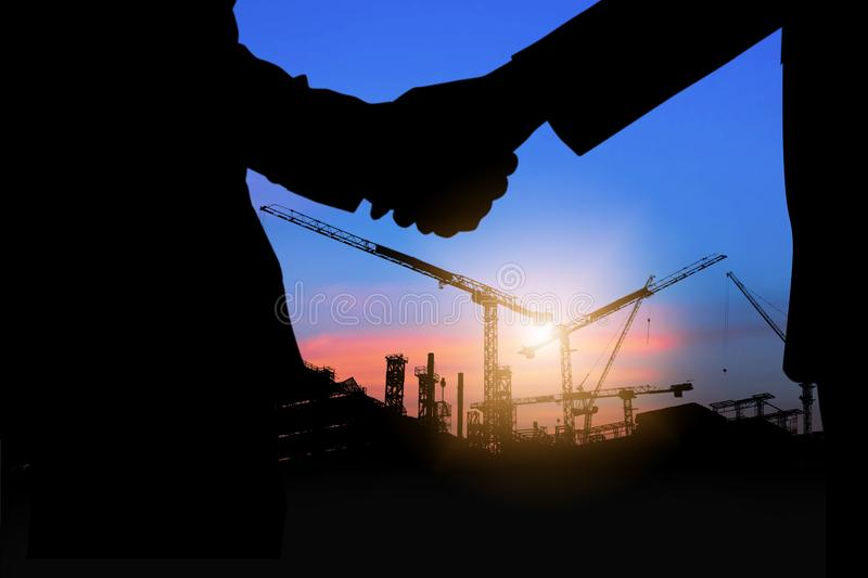 Silhouette shaking hands of investment people with engineer at working construction site stock image