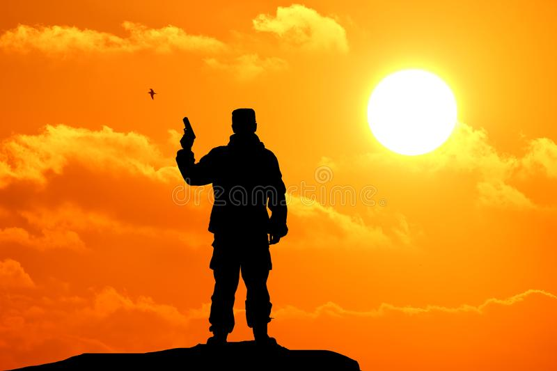 Silhouette shot of soldier holding gun royalty free stock photo