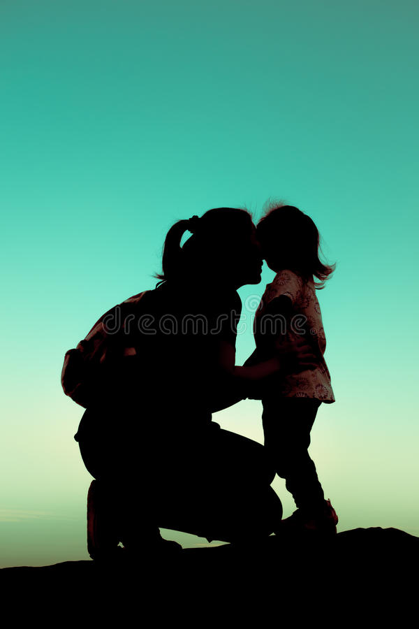Silhouette side view of a young mother lovingly kissing her little child. Cross process. stock photography