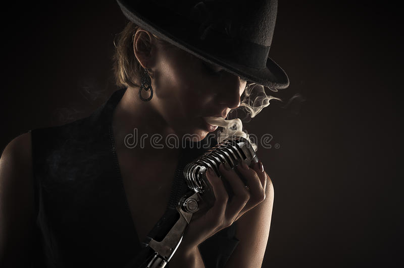 Silhouette singer woman with retro microphone. Closeup royalty free stock image