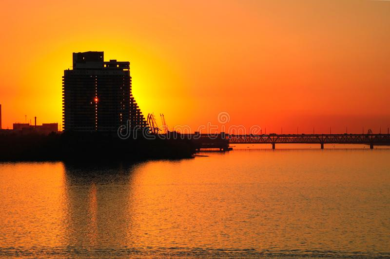 Silhouette of a skyscraper Sail and Old bridge of an orange sunset background, on the Dnieper River in the Dnipro city. Dnepropetrovsk, Dnepr, Ukraine stock photography