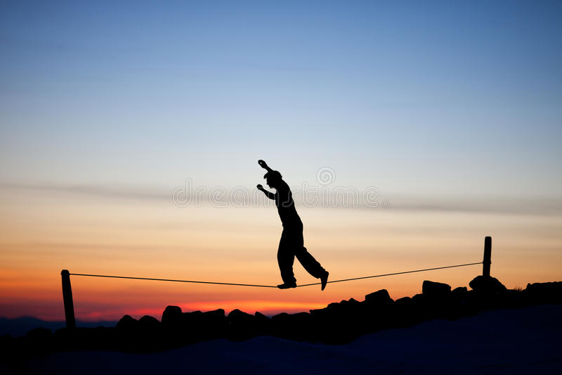 Silhouette of slackliner. In sunset sky stock image