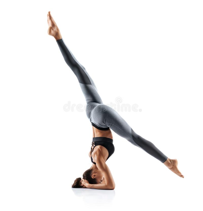 Silhouette of slim girl practicing yoga isolated on white background. stock photography