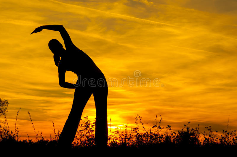 Silhouette Of The Slim Girl Stretching Out Stock Images