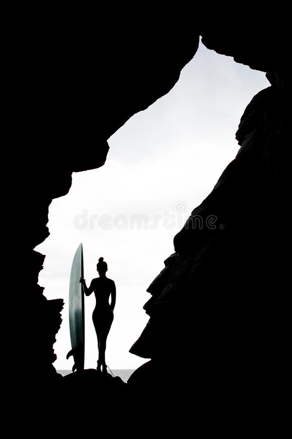 Silhouette slim girl in the swimsuit standing with the surf royalty free stock image