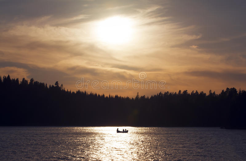 Silhouette of small boat in golden sunset. Silhouette of small fishing boat with three people in it, in golden sunset with shimmering water royalty free stock photography