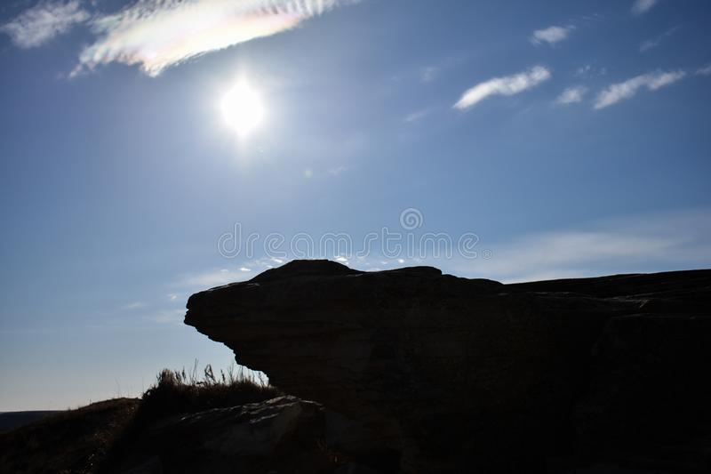 A silhouette of a small cliff edge hovers over a nature path. A silhouette of a small cliff edge is covered in shadow under a bright sun filling the sky with stock images