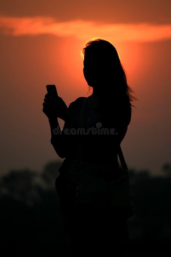 Silhouette smartphone азиатской женщины касающий на времени захода солнца стоковые изображения