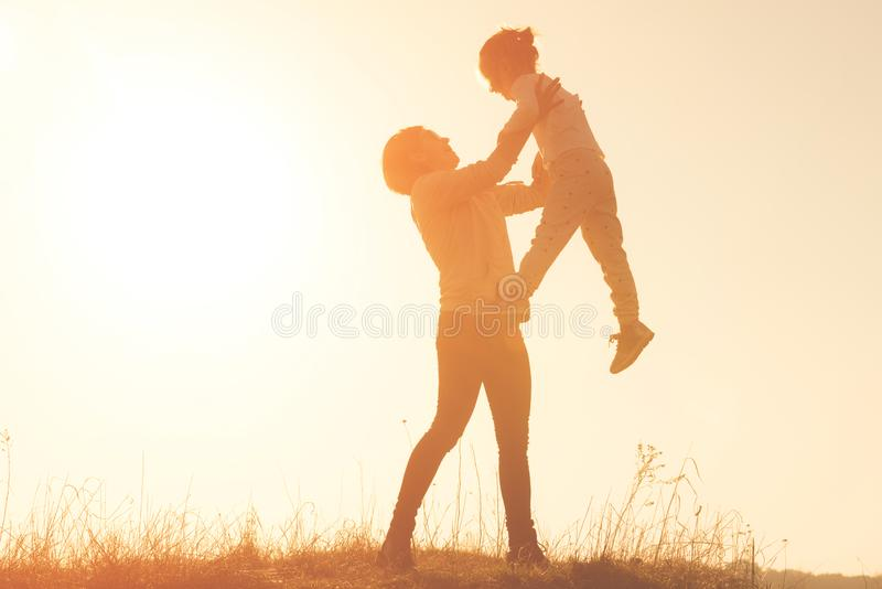 Silhouette of smilling young mother throwing up baby in the sky at sunset stock photo