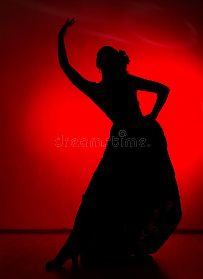 Silhouette of spanish girl flamenco dancer on a red background.  royalty free stock photo