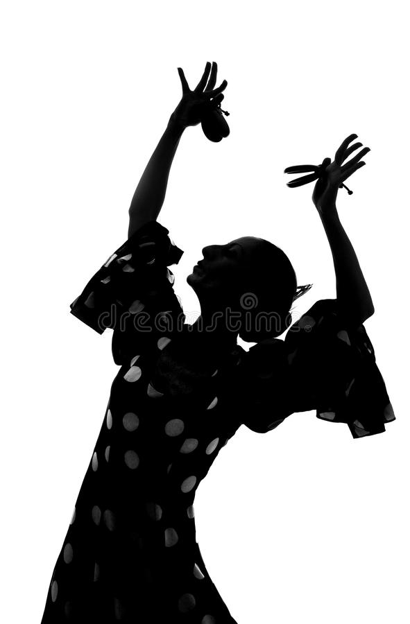 Silhouette of Spanish woman Flamenco dancer dancing Sevillanas. In gypsy dots dress and castanets in traditional Dance of Spain concept performing show isolated royalty free stock image