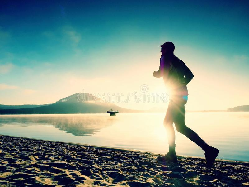 Silhouette of sport active man running on the lake beach at sunrise. Healthy lifestyle. stock photo