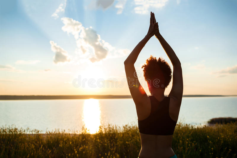 Silhouette of sportive girl practicing yoga in field at sunrise. Silhouette of young beautiful sportive girl practicing yoga in field at sunrise stock photos