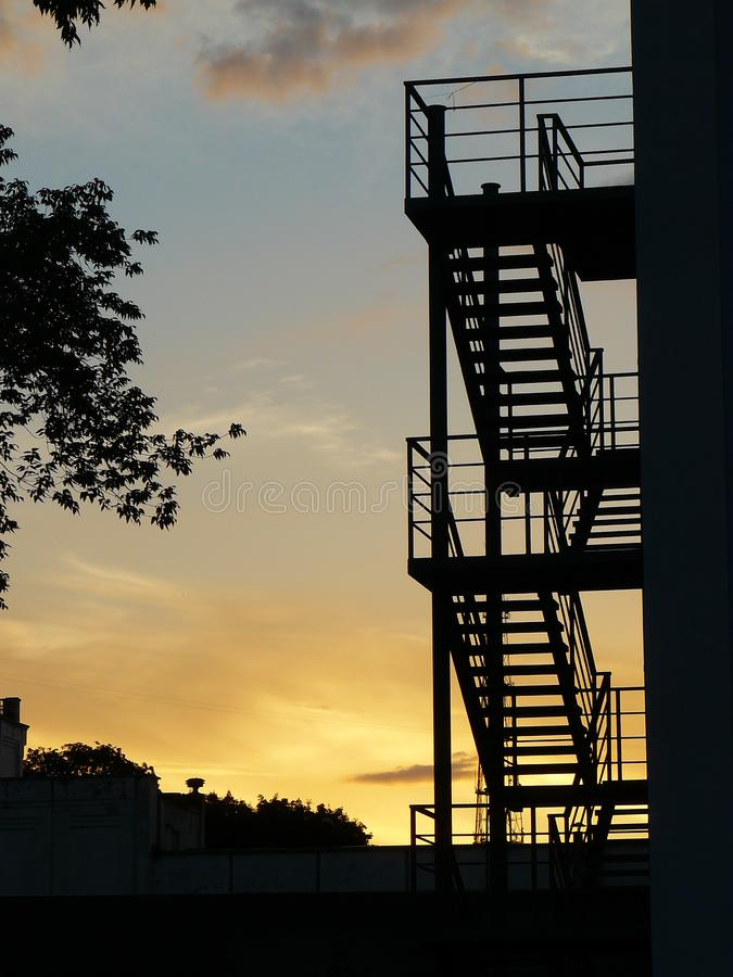 Silhouette of the stairs at sunset. Beautiful silhouette of the stairs, on the back of the house, beautifully lit by the last rays of the sun stock images