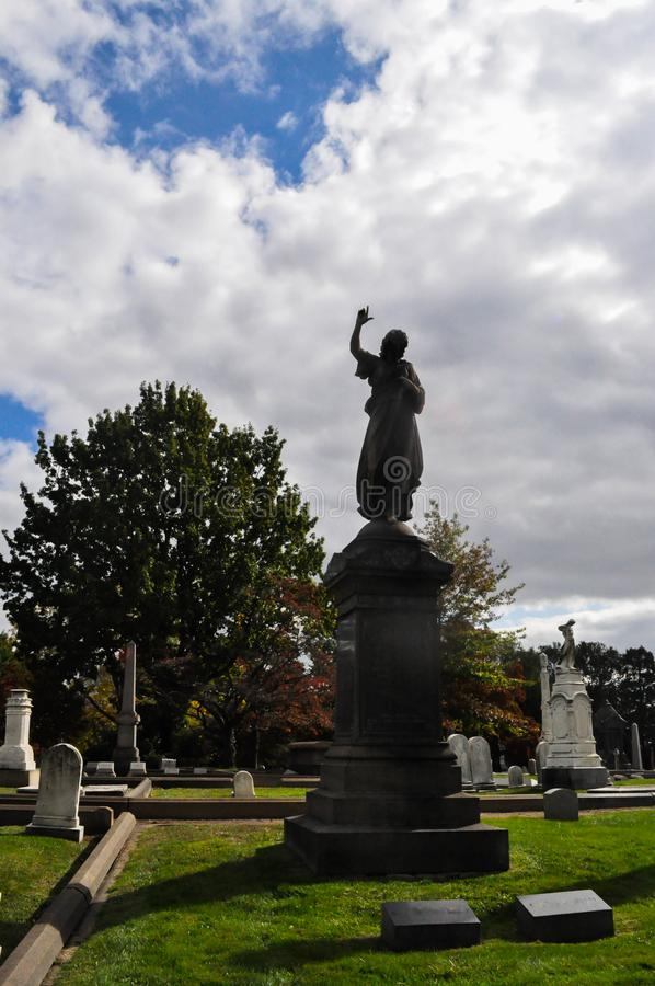 Silhouette Statue of an Angel Pointing Up in a Cemetery Landscape. Tall, silhouetted statue of an angel pointing up to the sky in a cemetery landscape stock photos