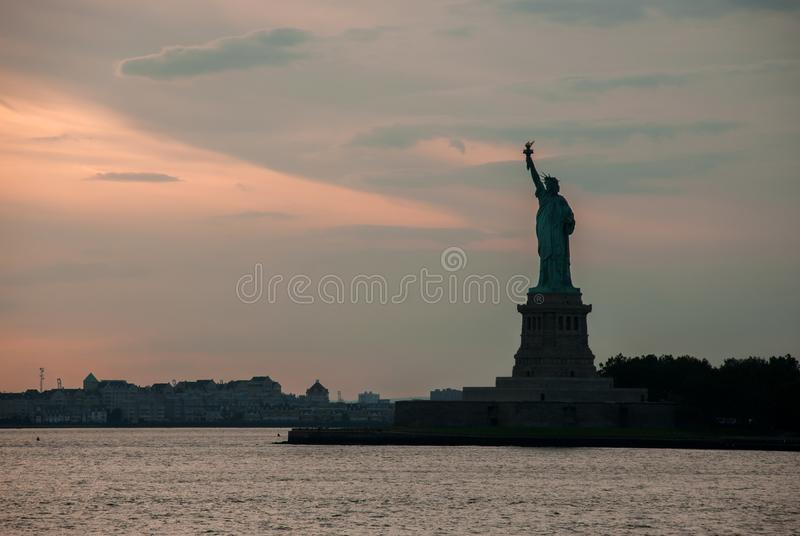Silhouette of Statue of Liberty at beautiful sunset stock image