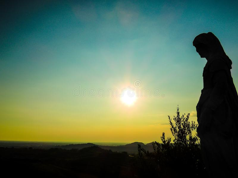 Silhouette of statue at sunset and view over friul vineyards at Abbey of Roses royalty free stock image