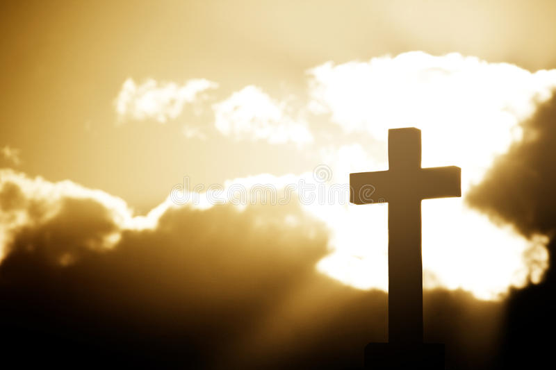 Silhouette of a stone cross in rays of sunlight royalty free stock photo