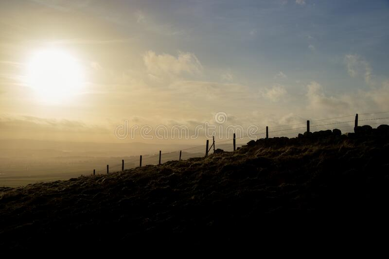 Silhouette of stone wall & fence against dramatic, cloudy sunset, Lomond Hills, Scotland. Silhouette of stone boundary wall & wire fence against dramatic, cloudy royalty free stock image