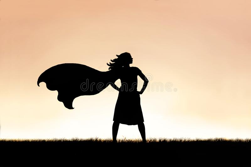 Strong Beautiful Caped Super Hero Woman Silhouette Isolated Against Sunset Sky Background royalty free stock images