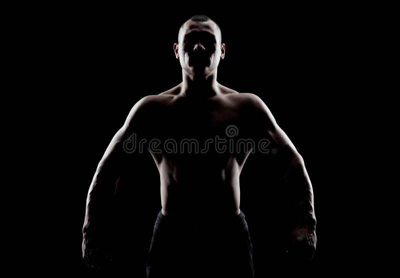 Silhouette of a strong man. Silhouette of a strong fighter. Confident young fitness man with strong hands and clenched fists stock image