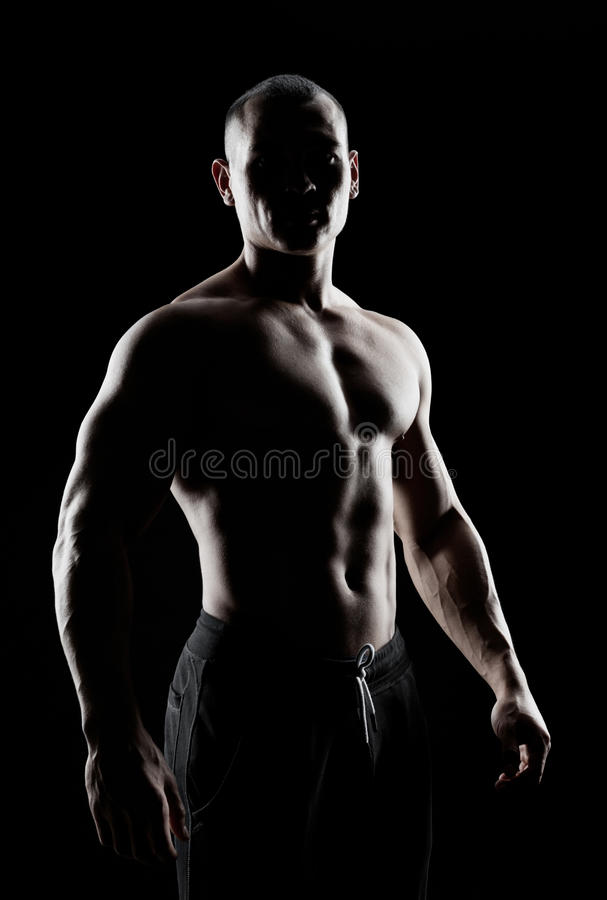 Silhouette of a strong man. Silhouette of a strong fighter. Confident young fitness man with strong hands and clenched fists royalty free stock photos