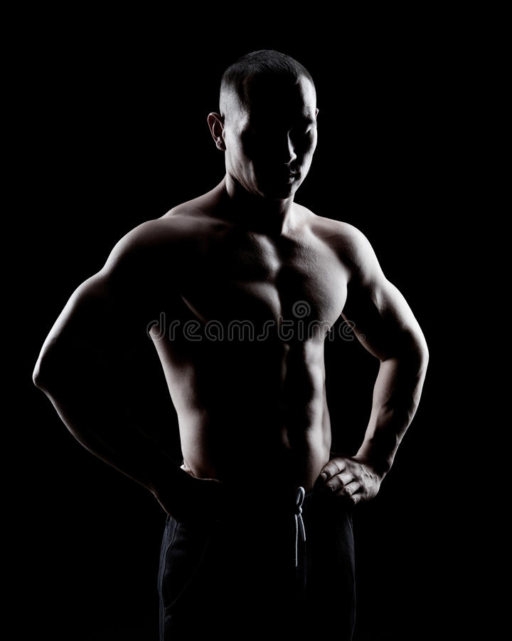 Silhouette of a strong man. Silhouette of a strong fighter. Confident young fitness man with strong hands and clenched fists royalty free stock image