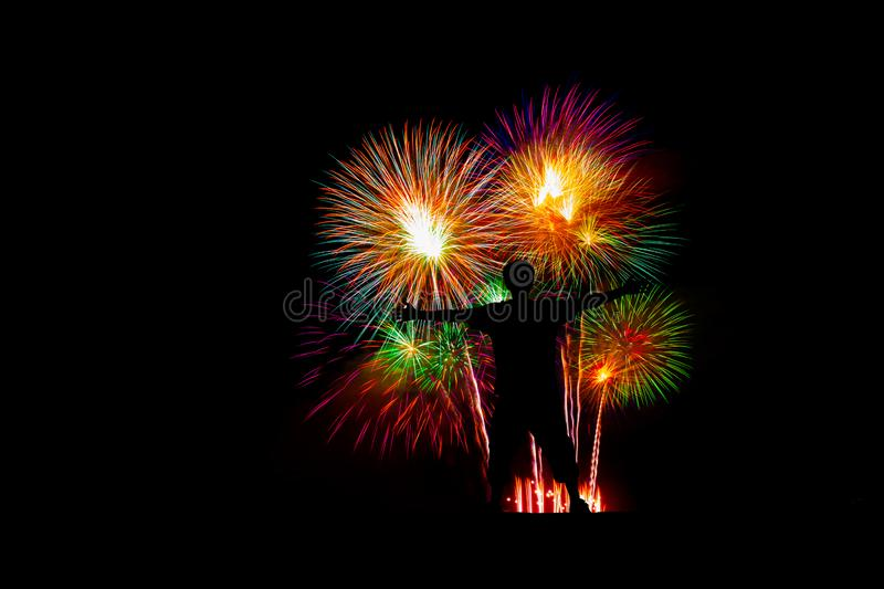 The man raised his two hands to show victory in the midst of fireworks. royalty free stock photos