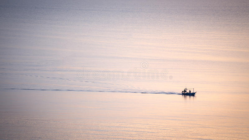 Silhouette sunrise of minimal fishery boat sail on calm sea stock image