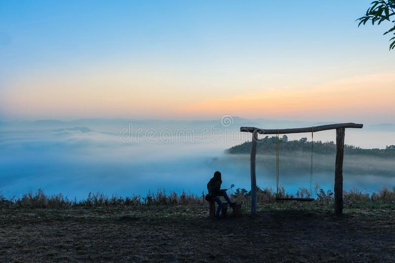 Silhouette the sunrise with the wooden swing, the fog, the tourist, the beautiful sky and cloud at Phu Lam Duan Mountain, Pak Chom royalty free stock images