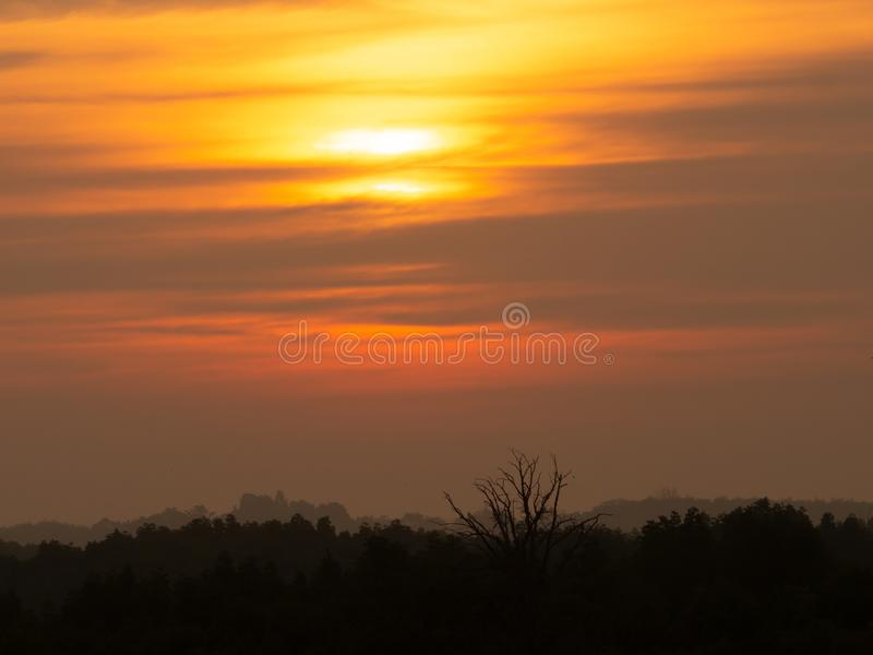 Silhouette sunset sky background. Twilight natural sunset sunrise over forest mountain. Warm color sky orange yellow royalty free stock image