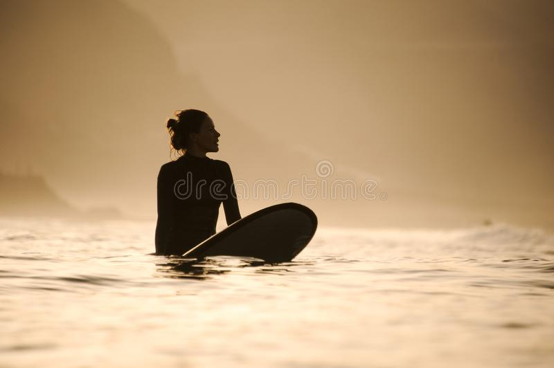 Silhouette of a surfer girl in the waters. Silhouette of a fit surfer girl with hair bun in the waters royalty free stock images