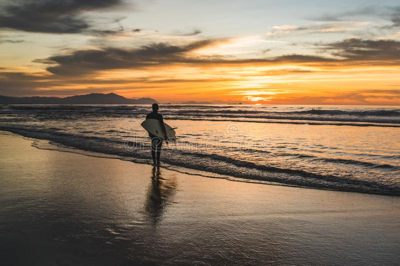 Silhouette of a surfer sitting on the beach of the Atlantic Ocean, near San Sebastian and Bilbao, North of Spain, Europe watching royalty free stock photo