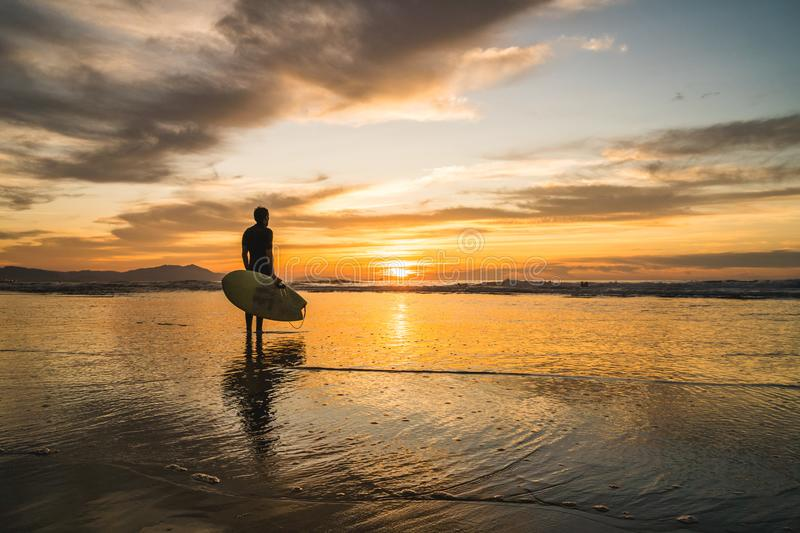 Silhouette of a surfer standing on the beach of the Atlantic Ocean, near San Sebastian and Bilbao, North of Spain, watching a royalty free stock image