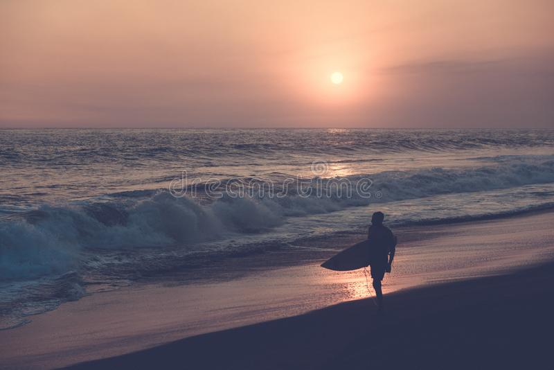 Silhouette of surfer walking at beach with sunset royalty free stock images