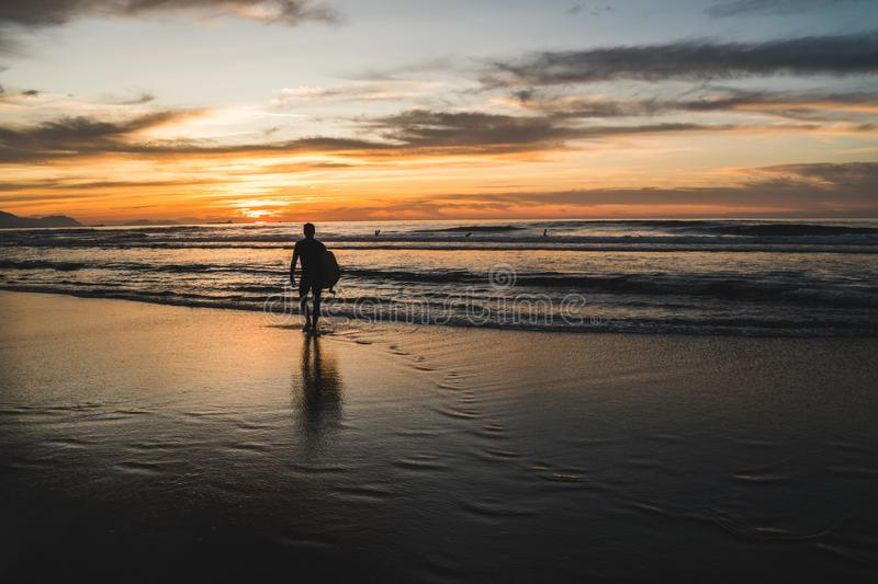 Silhouette of a surfer walking towards the waves of the Atlantic Ocean, near San Sebastian and Bilbao, North of Spain, watching a royalty free stock photo
