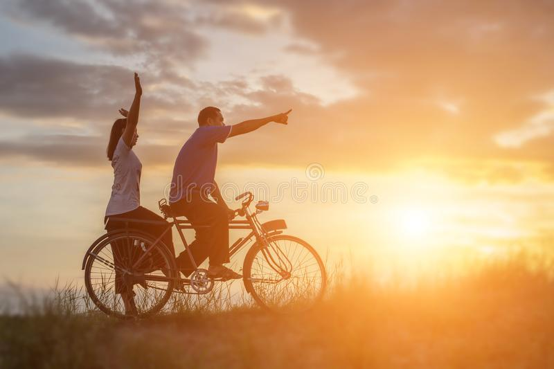 Silhouette of sweet young couple in love happy time on bicycle stock image