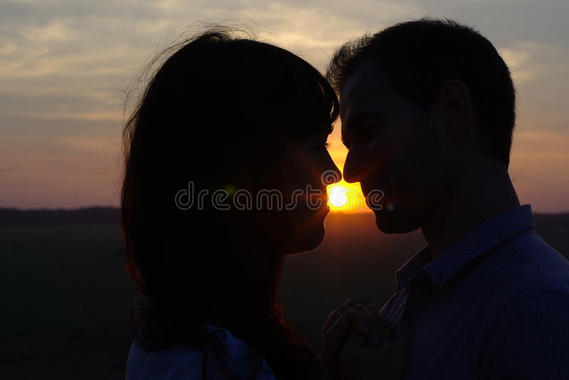 Silhouette sweethearts kissing at sunset royalty free stock photography